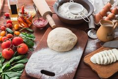 Step-by-step boss makes a pizza margarita. Dough and pizza ingredients royalty free stock image