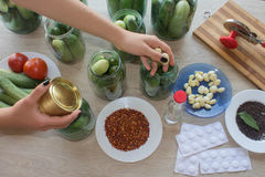 Step by step, the flavors come together. A woman hands are hard at work, stuffing cucumbers and dill into a pickling jar as she pr Royalty Free Stock Photo