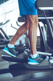 Step by step to get fit. Side view part of young man in sports shoes working out on stepper at gym Royalty Free Stock Photos