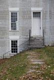 Step stone pathway leads to white antique door. Stock Photos