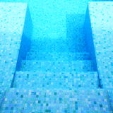 Step into swimming pool. Mosaic tiles on the step into a private swimming pool Stock Image