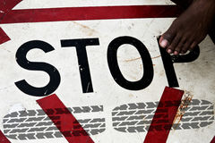 Step to stop. Foot steps onto a stop sign Stock Image