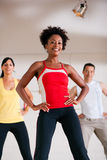 Step Training in gym with instructor. Group of three people in colorful cloths in a gym doing step gymnastics, a female instructor in front Royalty Free Stock Photo