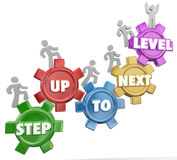 Step Up to Next Level Gear Marchers Rising Success Achievement. Step Up to Next Level in 3d words on gears as people rise to achieve success through several Stock Photography