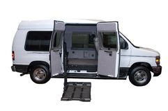 Step Van Handicap Wheelchair Lift Isolated. Isolated step utility van with the doors open and load lift deployed. Lift is used for heavy loads or giving the Royalty Free Stock Image