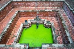 A step-well in Nepal is filled with bright green algae royalty free stock image