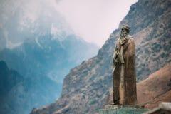 Stepantsminda, Geórgia Estátua de Alexander Kazbegi And Mountain fotos de stock royalty free