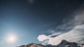 Stepantsminda, Geórgia O céu estrelado da noite do inverno com estrelas e pico de incandescência da montagem Kazbek cobriu com a  video estoque