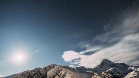Stepantsminda, Geórgia O céu estrelado da noite do inverno com estrelas e pico de incandescência da montagem Kazbek cobriu com a  filme