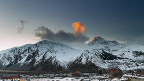 Stepantsminda, Geórgia Pico da montagem Kazbek durante o por do sol Casas famosas da igreja e do campo de Gergeti no inverno vídeos de arquivo