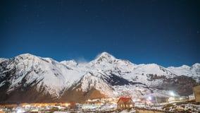 Stepantsminda, Georgia Небо ночи зимы звездное с накаляя звездами и пиком держателя Kazbek покрыло со снегом красивейше акции видеоматериалы