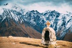 Stepantsminda, Georgia Cruz en piedras en fondo de las montañas imagen de archivo