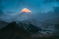 Stepantsminda, Georgia Soporte Kazbek por la mañana iluminada por el sol y Famou foto de archivo