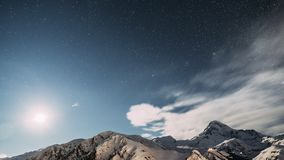 Stepantsminda, Georgia. Winter Night Starry Sky With Glowing Stars And Peak Of Mount Kazbek Covered With Snow. Beautiful stock footage