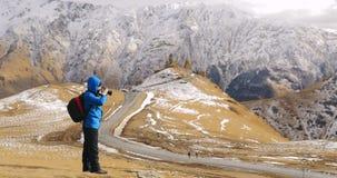 Stepantsminda, Gergeti, Geórgia Fotógrafo Taking Pictures Photos do viajante do mochileiro do turista do homem da trindade santam vídeos de arquivo