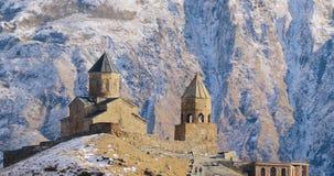 Stepantsminda, Gergeti, Geórgia Igreja famosa de Tsminda Sameba da trindade de Gergeti em Autumn Landscape atrasado Bonito filme