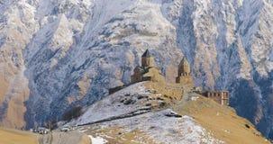 Stepantsminda, Gergeti, Geórgia Igreja famosa de Tsminda Sameba da trindade de Gergeti em Autumn Landscape atrasado Bonito vídeos de arquivo