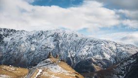 Stepantsminda, Gergeti, Geórgia Igreja famosa de Tsminda Sameba da trindade de Gergeti na paisagem adiantada do inverno Bonito vídeos de arquivo