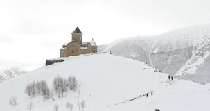 Stepantsminda, Gergeti, Georgia Известная церковь Tsminda Sameba троицы Gergeti в ландшафте зимы видеоматериал