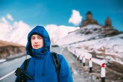 Stepantsminda, Gergeti, Georgia Фотограф путешественника Backpacker человека туристский представляя около церков святой троицы -  стоковое изображение