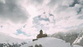 Stepantsminda, Gergeti, Georgia Iglesia famosa de Tsminda Sameba de la trinidad de Gergeti en paisaje del invierno metrajes
