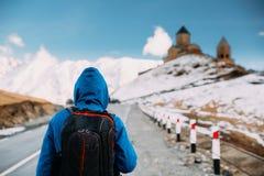 Stepantsminda, Gergeti, Georgia Viaggiatore turistico di viaggiatore con zaino e sacco a pelo dell'uomo immagine stock