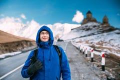 Stepantsminda, Gergeti, Georgia Viaggiatore turistico di viaggiatore con zaino e sacco a pelo dell'uomo fotografia stock libera da diritti