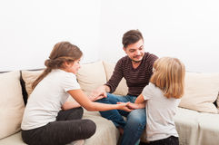 Stepfather having fun with step daughters. On the couch or sofa Stock Photography