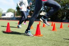 Steping over oranje kegels tijdens praktijk Stock Foto's