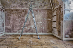 Stepladders in a room that is being decorated. A room has been stripped of carpets and wallpaper during interior decoration,. Metal stepladders stand on bare Royalty Free Stock Images