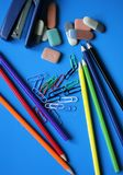Stepler, erasers, colored pencils and clips. On the blue background Stock Photography