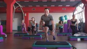 Stepp-Aerobic-Übungsklasse - Gruppe von Personen, die auf Steppers mit dem Trainer trainiert stock video
