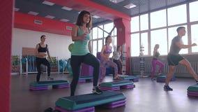 Stepp-Aerobic-Übungsklasse - Gruppe von Personen, die auf Steppers mit dem Trainer trainiert stock footage