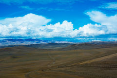 Steppe landscape with a road, mountains, blue sky stock photography