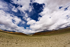 Steppe mountains sky. Steppe semi desert landscape of Altai mountains (Russia): dry earth with rare plants as a foreground and mountains at the scyline with sky Stock Photos