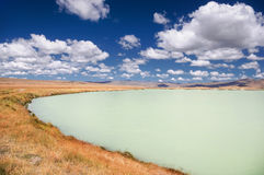 Steppe shore of a milky turquoise glacier lake with dry grass. Steppe shore of a milky turquoise glacier lake with dry yellow grass under the blue sky and white royalty free stock photos