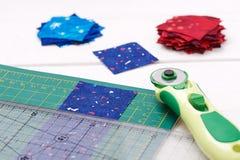 Steppende Werkzeuge, Stück Gewebe vorbereitet zum Schnitt, zwei Haufen abgeschnitten von den Geweben Lizenzfreies Stockfoto