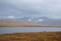 Steppenufer von einem See mit trockenem gelbem Gras auf dem Hintergrund von hohen Felsenbergen Stockbild