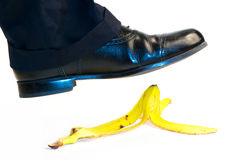 Stepping on banana peel. A studio view of a large foot and shoe about to step on a yellow banana peel.  Isolated on white background Stock Images