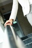 Stepping down. Image of female hand holding by banisters while going down in office building Stock Images