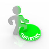 Stepping Onto the Confidence Button. A person steps onto a green button marked Confidence Stock Images
