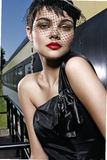 Stepping out on a train. Beautiful young lady models vintage fashion at train station Stock Images