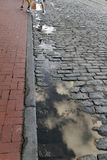Stepping Over Cobblestone Puddles Royalty Free Stock Images
