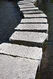 Stepping stones. Ancient stepping stones on water creating a path Stock Image