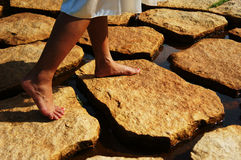 Stepping on Stones. Girl with dress without shoes stepping on stones on water Royalty Free Stock Photos