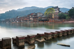 Stepping stones across the Tuojiang river with the North Gate Tower in the background in Fenghuang, Hunan Province, China Stock Image