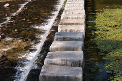 Stepping stones cross over a stream Stock Photo