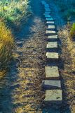Stepping stones on a dusty pathway stock images