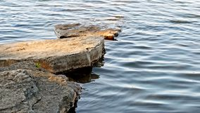 Stepping stones of flat natural rock leading out into beautiful lake Stock Photography