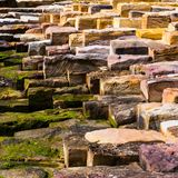 These Stepping Stones. Large stone steps in various colours placed in a geometrical pattern near the seaside stock photos
